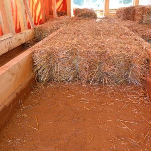 izolace podlah balíky slámy na závětrné vrstvě tvořené jutou máčenou v jílu
