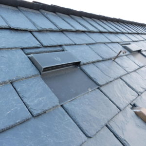 břidlicová střecha z masivních obdélníkových šablon, ukončení hřebene postaru přesahem